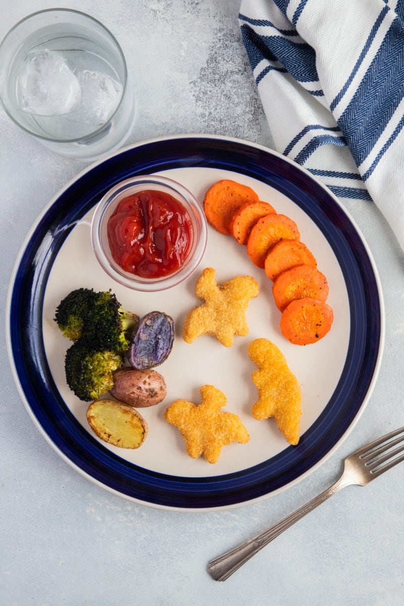 Yummy Dino Buddies with roasted vegetables on a plate. Lunch for picky eaters.