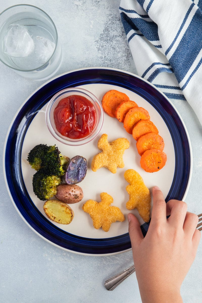 Yummy Dino Buddies with roasted vegetables on a plate and child hand reaching to grab one.