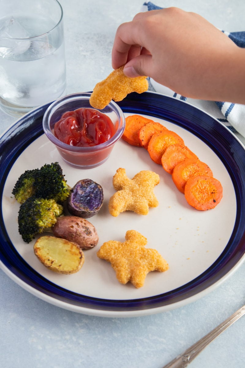 Kid's hand dipping a Yummy Dino Buddy nugget into ketchup
