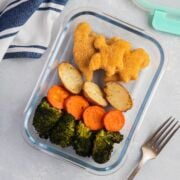 Yummy Dino Buddies with roasted vegetables on a glass food container