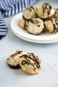 coconut macaroons on a board with white plate filled with cookies in the background