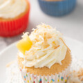 Coconut tres leches cupcake with whipped cream filling and topped with coconut flakes and pineapple