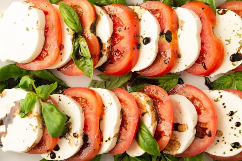 close view of juicy tomatoes and creamy mozzarella drizzled with balsamic vinegar