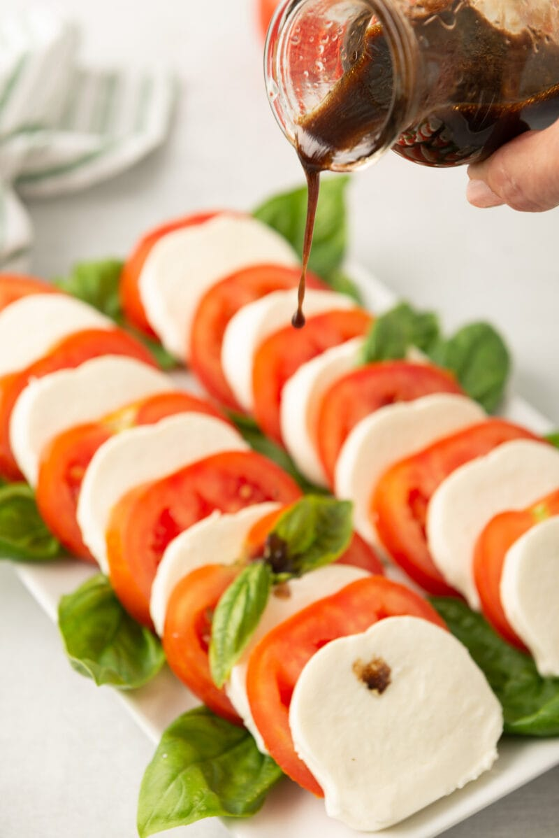 drizzling balsamic vinegar over the salad