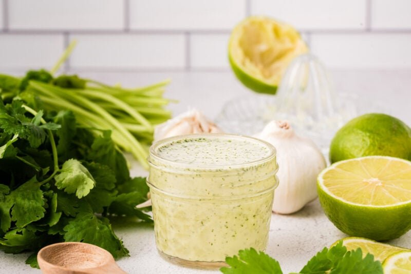Cilantro dressing on a work surface in a glass jar next to the ingredinets