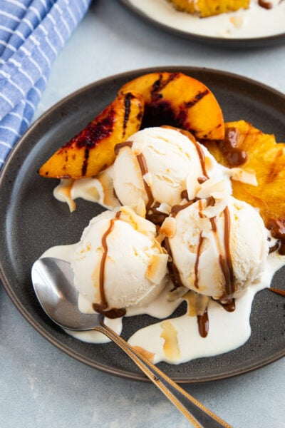 grilled pineapple and peaches with vanilla ice cream and dulce de leche on a grey plate