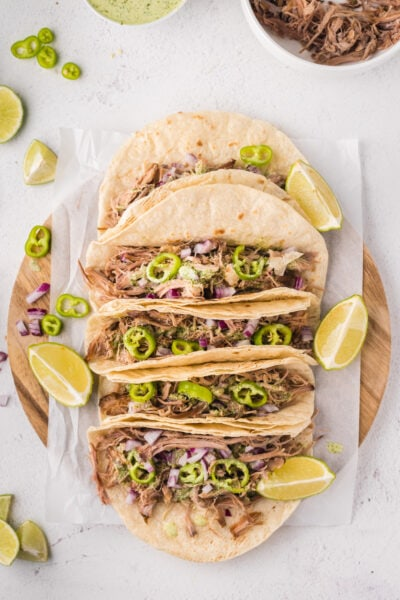 Overhead shot of five tacos on a wooden chopping board