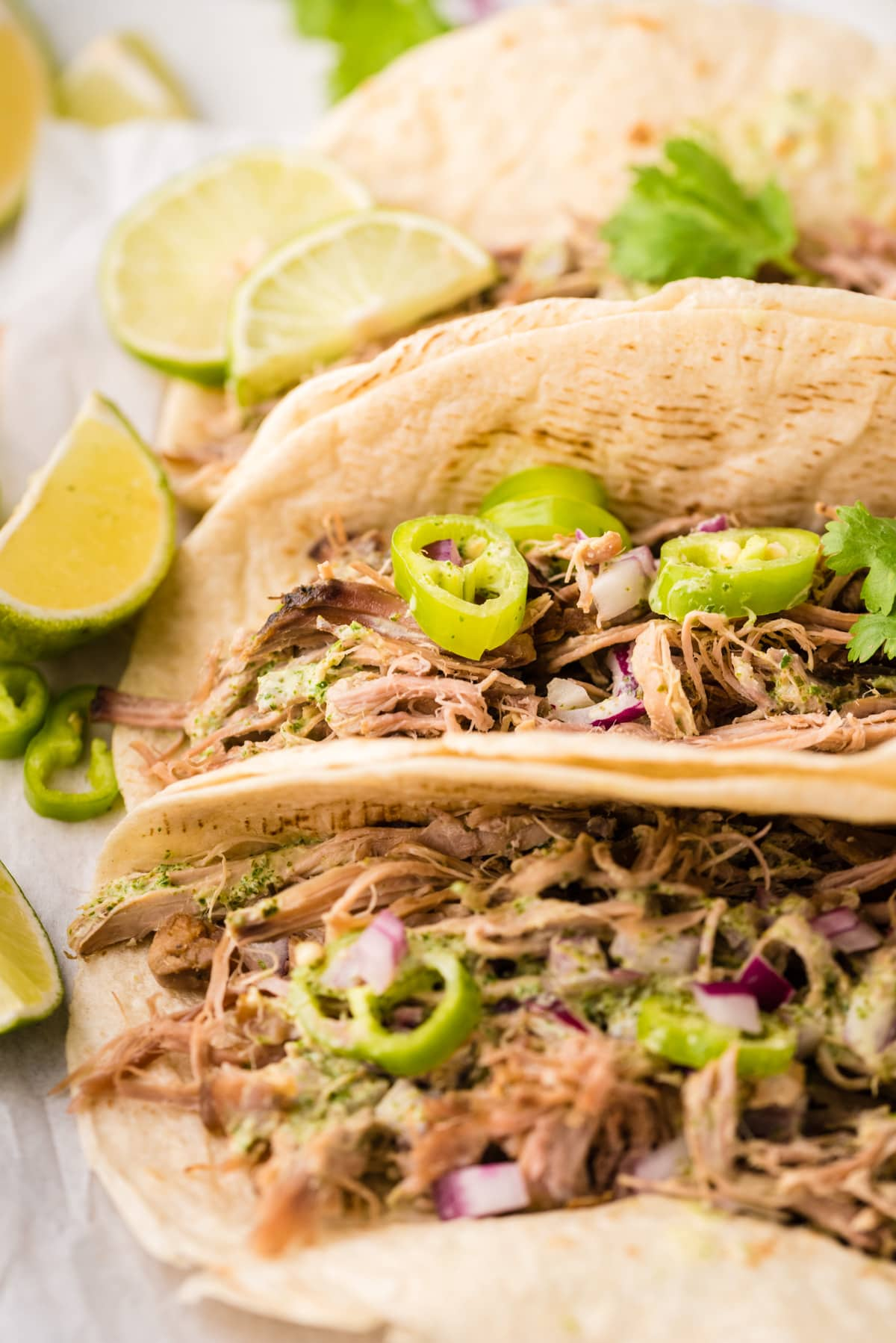 Close up of three pork tacos with toppings
