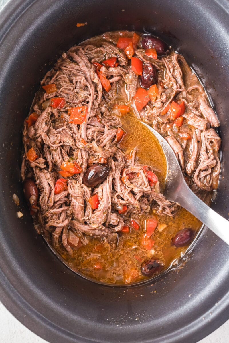A spoon stirring the shredded beef in a slow cooker