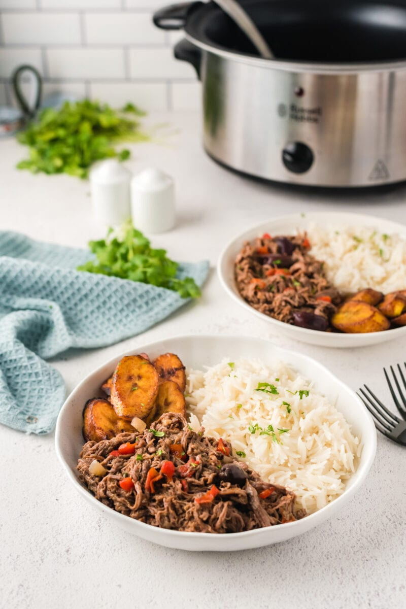 Two bowls of shredded beef in front of a slow cooker
