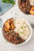 Shredded beef served in two bowls with rice and plantain