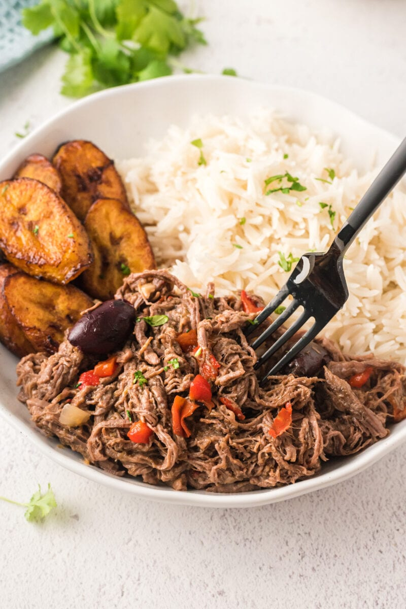 The shredded beef being eaten with a fork