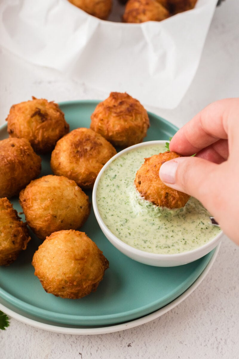 A yuca ball being dipped into a green sauce
