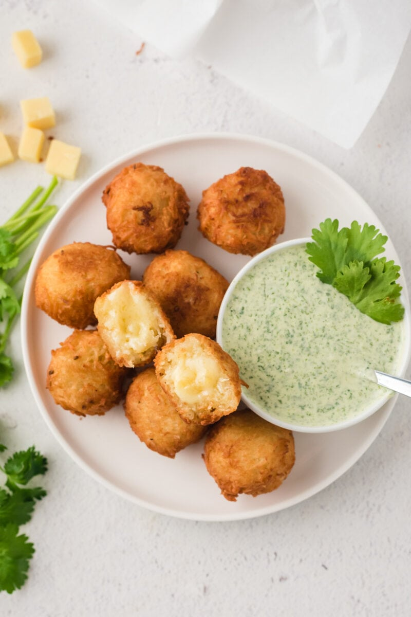Overhead shot of stuffed yuca balls served on a white plate with a dip