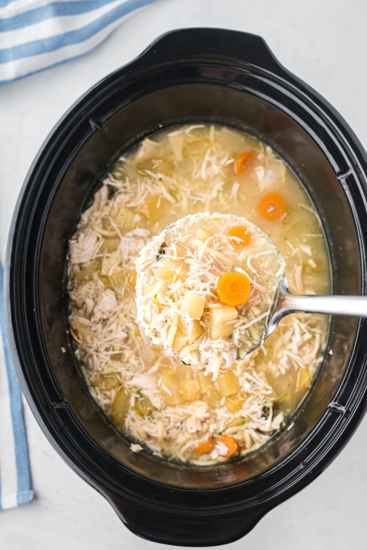 Un cucharón que saca un poco de sopa de la olla de barro.