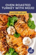 A whole carved roasted turkey on a platter with fresh herbs. Pinterest 2