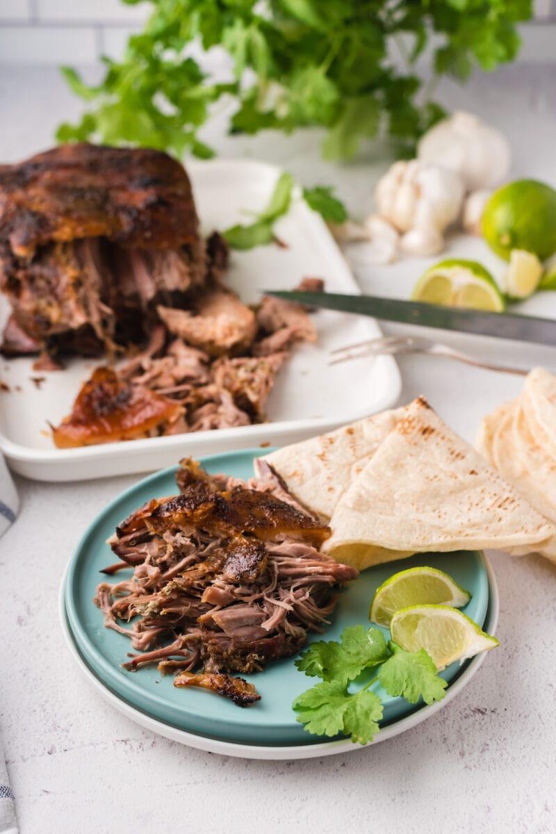 Crispy shredded pork on a plate with a tortilla and fresh herbs