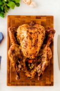 A whole mojo roasted turkey on a wooden chopping board.