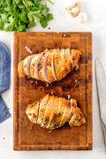 Two turkey breasts sliced on a chopping board.