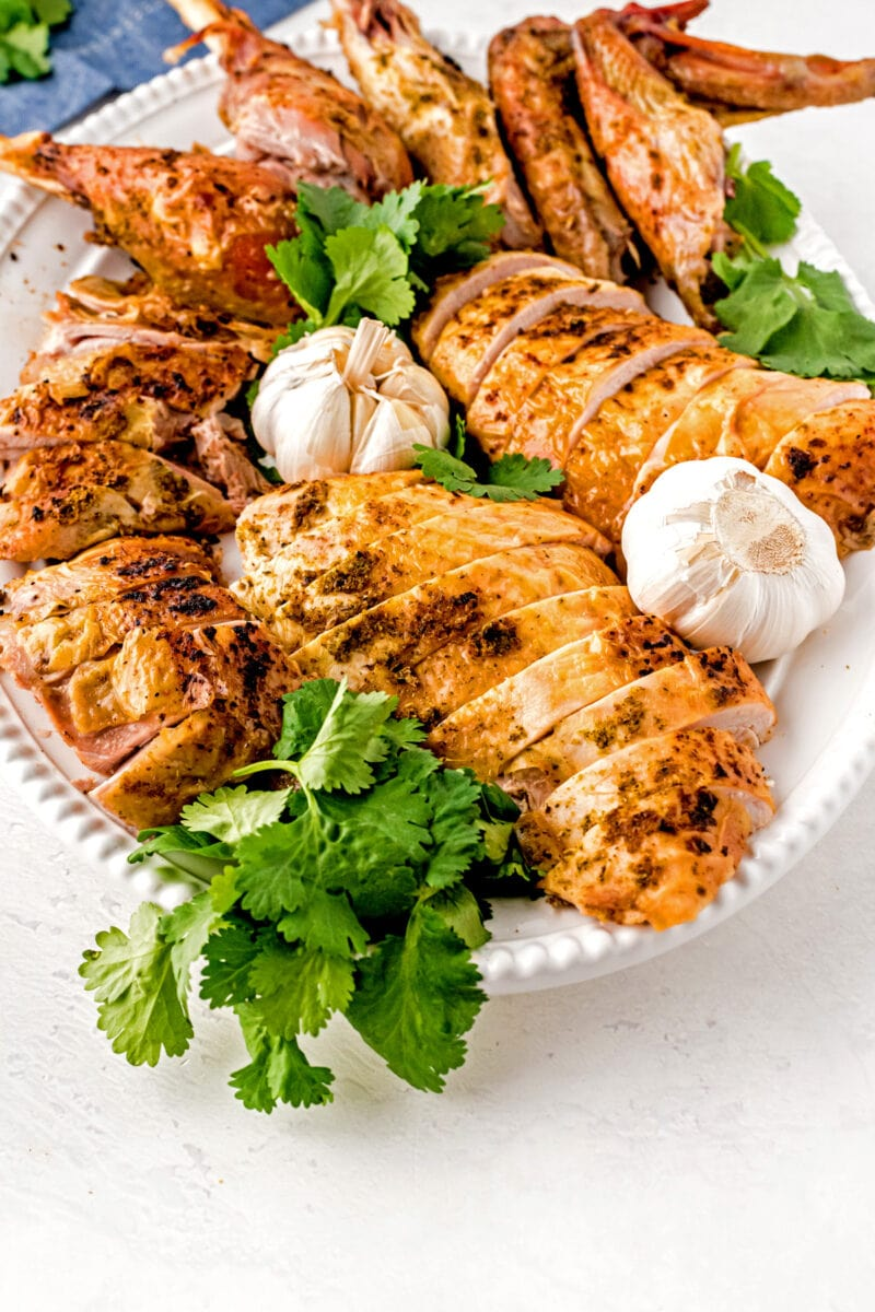 A whole carved roasted turkey on a platter with fresh herbs.