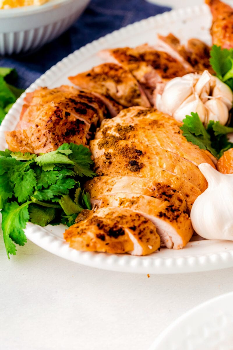 Pieces of carved turkey on a plate with fresh herbs and garlic bulbs