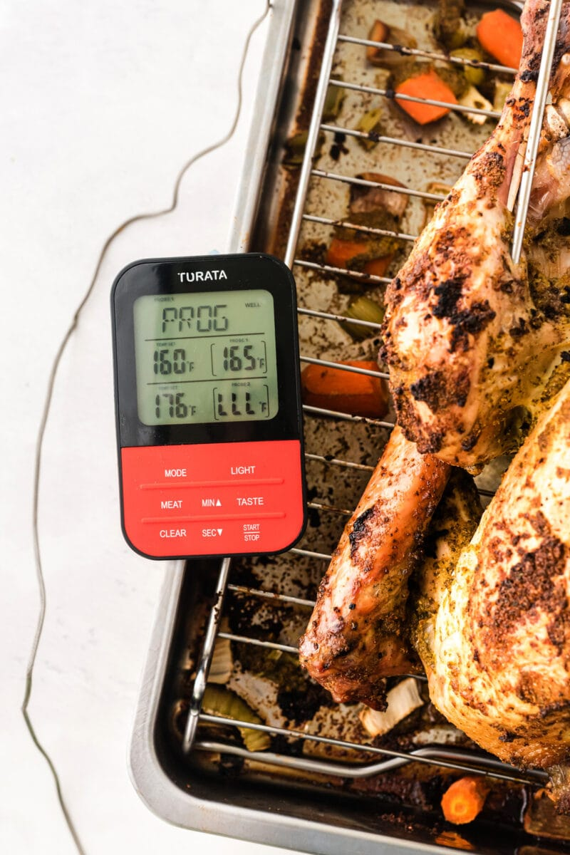 An instant read thermometer testing the temperature of the roasted turkey.