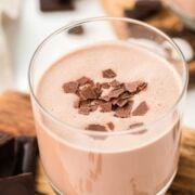 A glass of coquito topped with chocolate flakes.