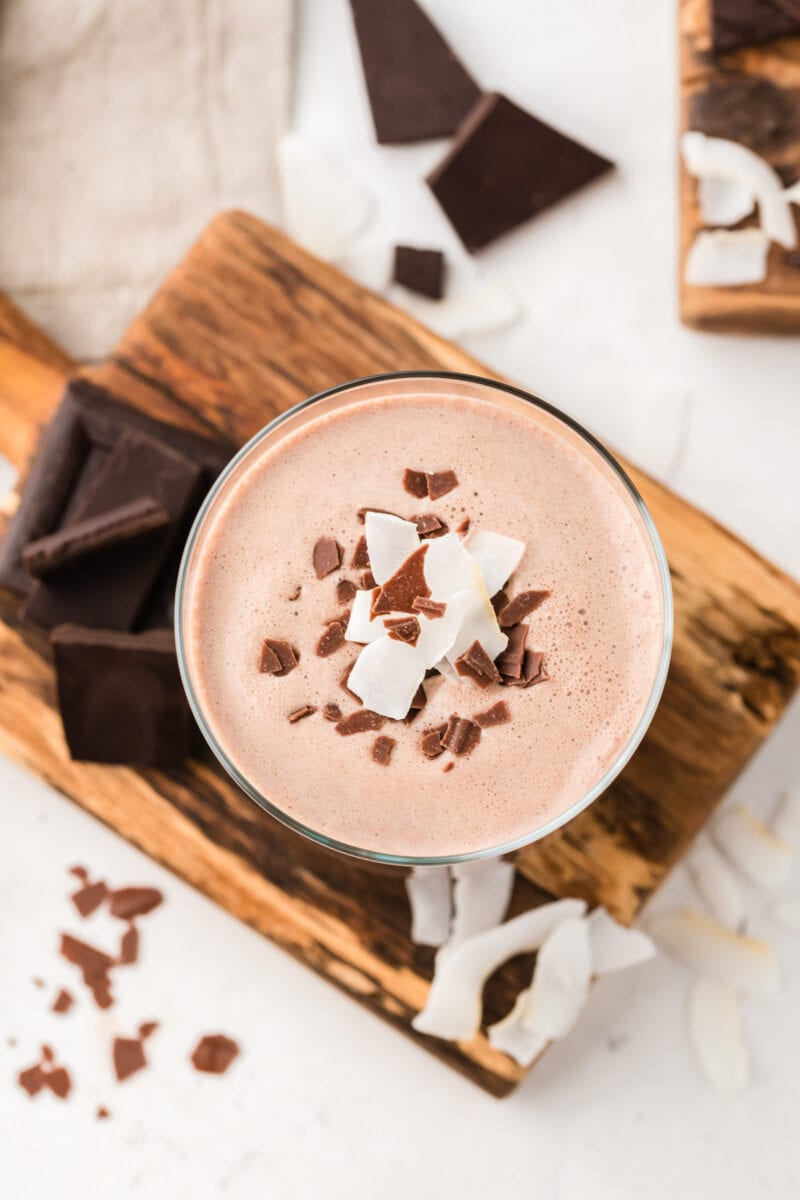 Overhead shot of a glass of chocolate coquito garnished with chocolate.