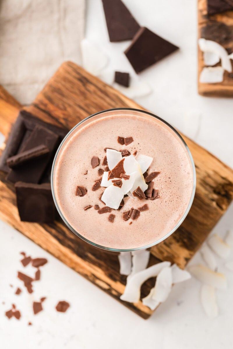 Fotografía superior de un vaso de coquito de chocolate con guarnición de chocolate.