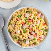 Pasta salad with peas and ham served in a white bowl.