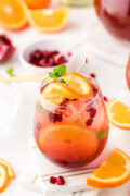 A glass of sangria next to slices of oranges and pomegranate seeds.