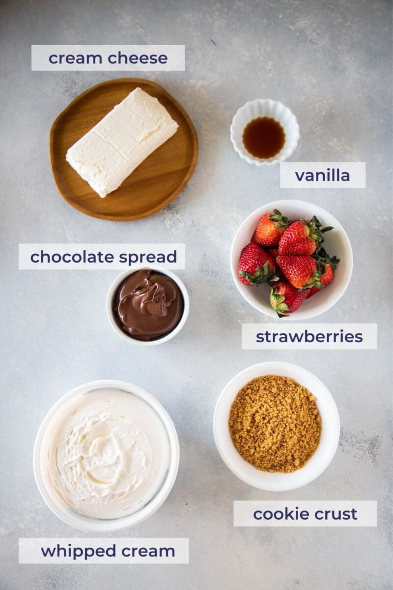 chocolate and strawberry cheesecake parfait ingredients on a board