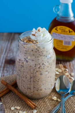 French Toast Overnight Oats served in a mason jar topped with whipped cream and a sprinkled of cinnamon.