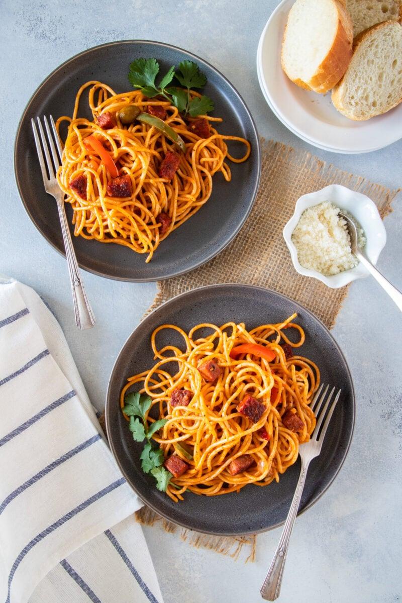 Dos platos de espaguetis servidos y listos para comer con una guarnición de pan