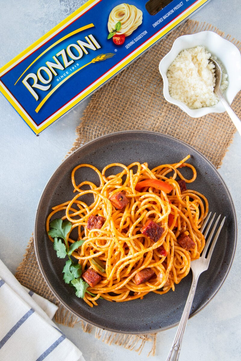 Espaguetis servidos listos para comer con una guarnición de queso parmesano