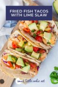 Delicious Fish Tacos made with a lime-dressed slaw, flounder fishand topped with avocado and a tomato, jalapeño and cilantro salsa all wrap in corn tortillas. Pinterest graphic