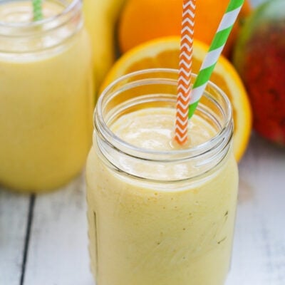 Mango Banana Smoothie served in a mason jar with paper straws