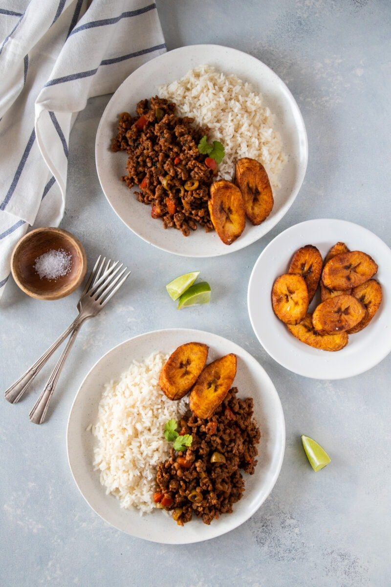 Two plates of picadillo served with rice and plantains