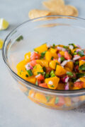 close up of peach salsa in a clear bowl ready to eat