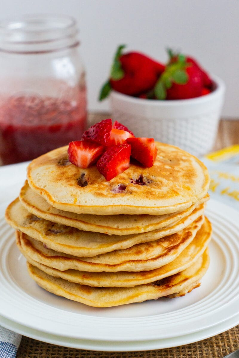stacked pancakes topped with fresh strawberries