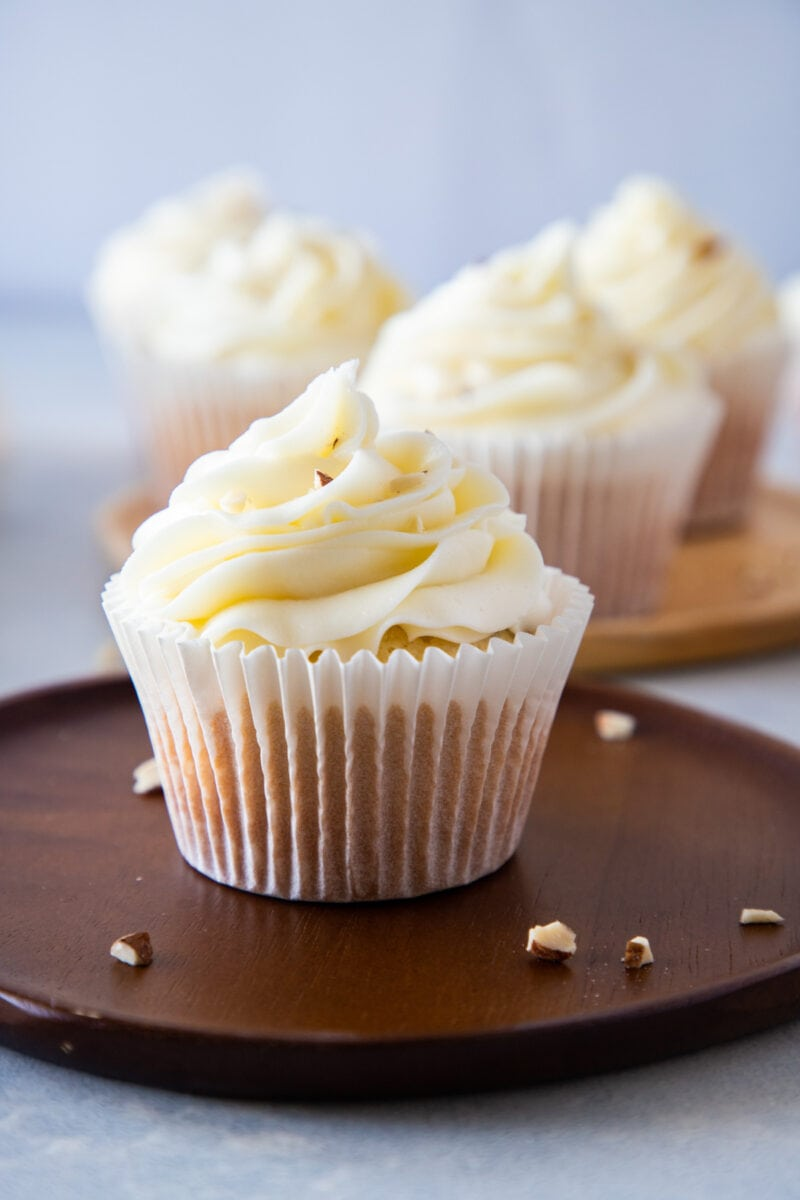 almond cupcakes with cream cheese frosting on a wooden plate sprinkled with chopped almonds