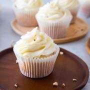 almond cupcakes with cream cheese frosting on a wooden plate ready to eat