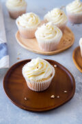 almond cupcakes with cream cheese frosting on a wooden plate