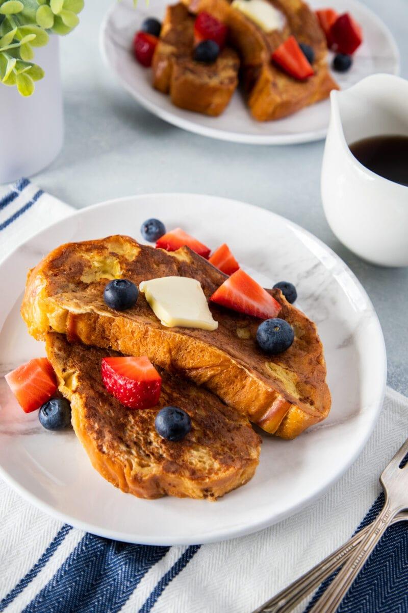 Tostada francesa de pan jalá servida en un plato con mantequilla y bayas