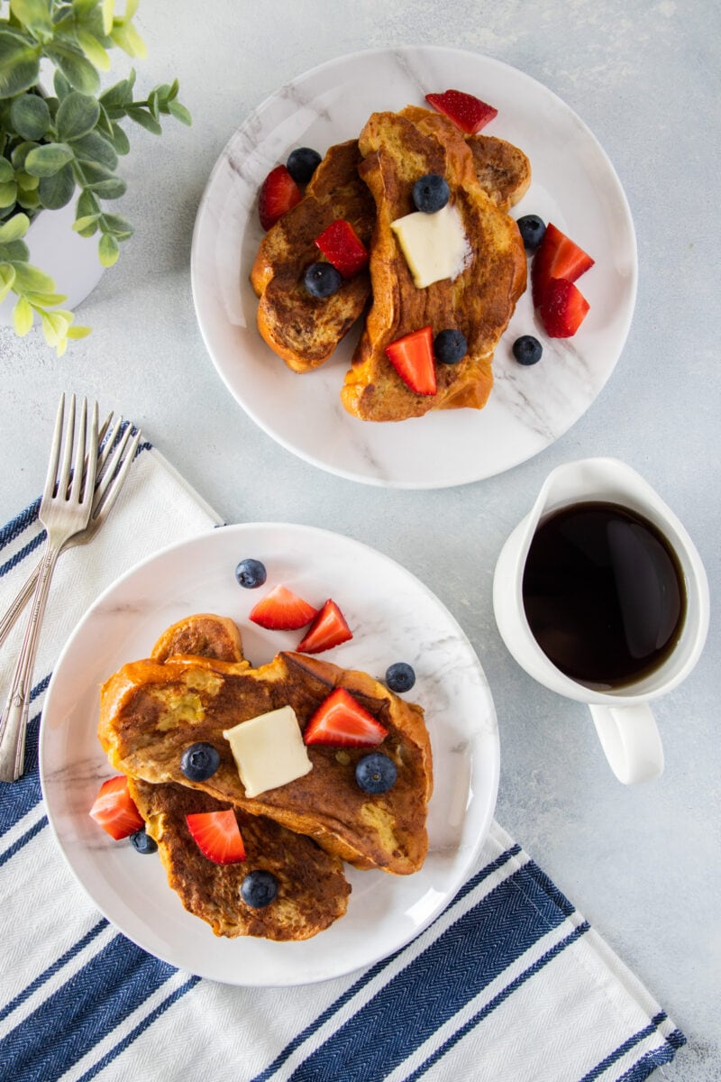 Challah Bread French Toast on a plate topped with berries and syrup on the side