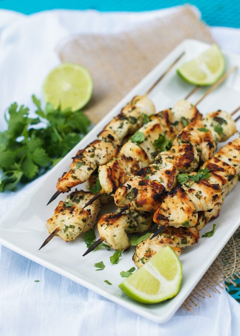chicken skewers served on a white platter with lime wedges on the side and cilantro for garnish