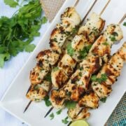 Chicken skewers served on a white plate with lime wedges on the side