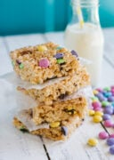 Stacked M&M rice krispies squares with a cup of milk on the side