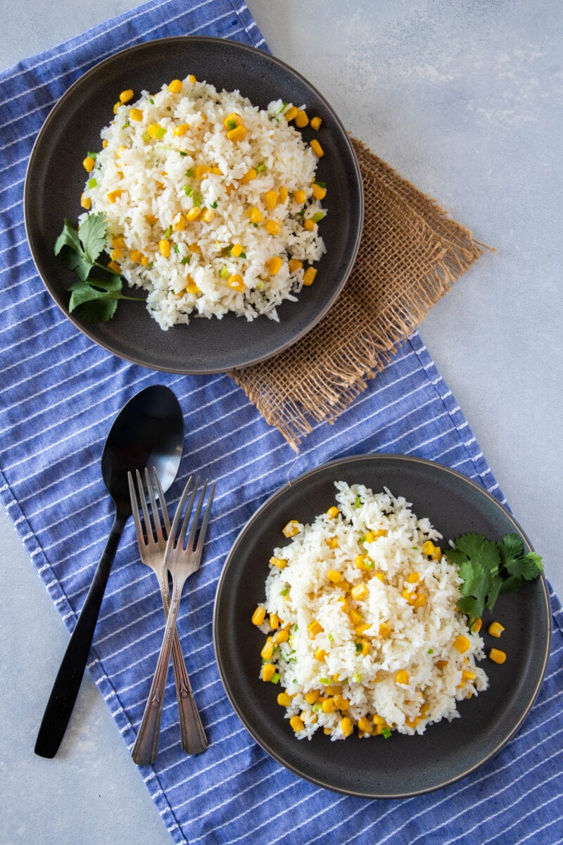 Rice with corn served in two gray plates with forks on the side