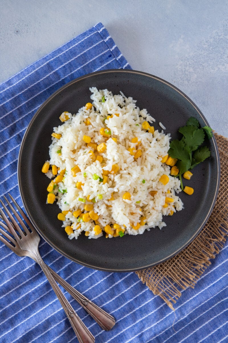 Rice with corn served on a gray plate ready to eat